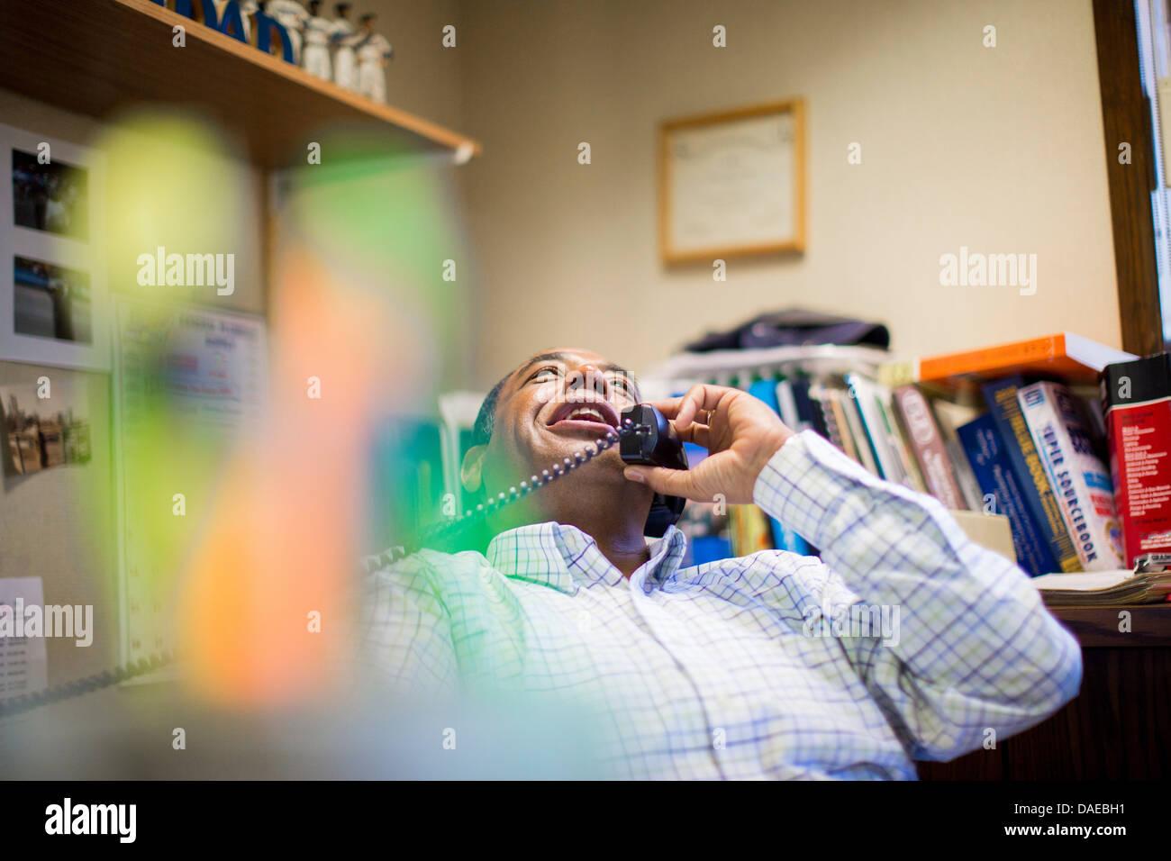 Male office worker enjoying landline conversation - Stock Image