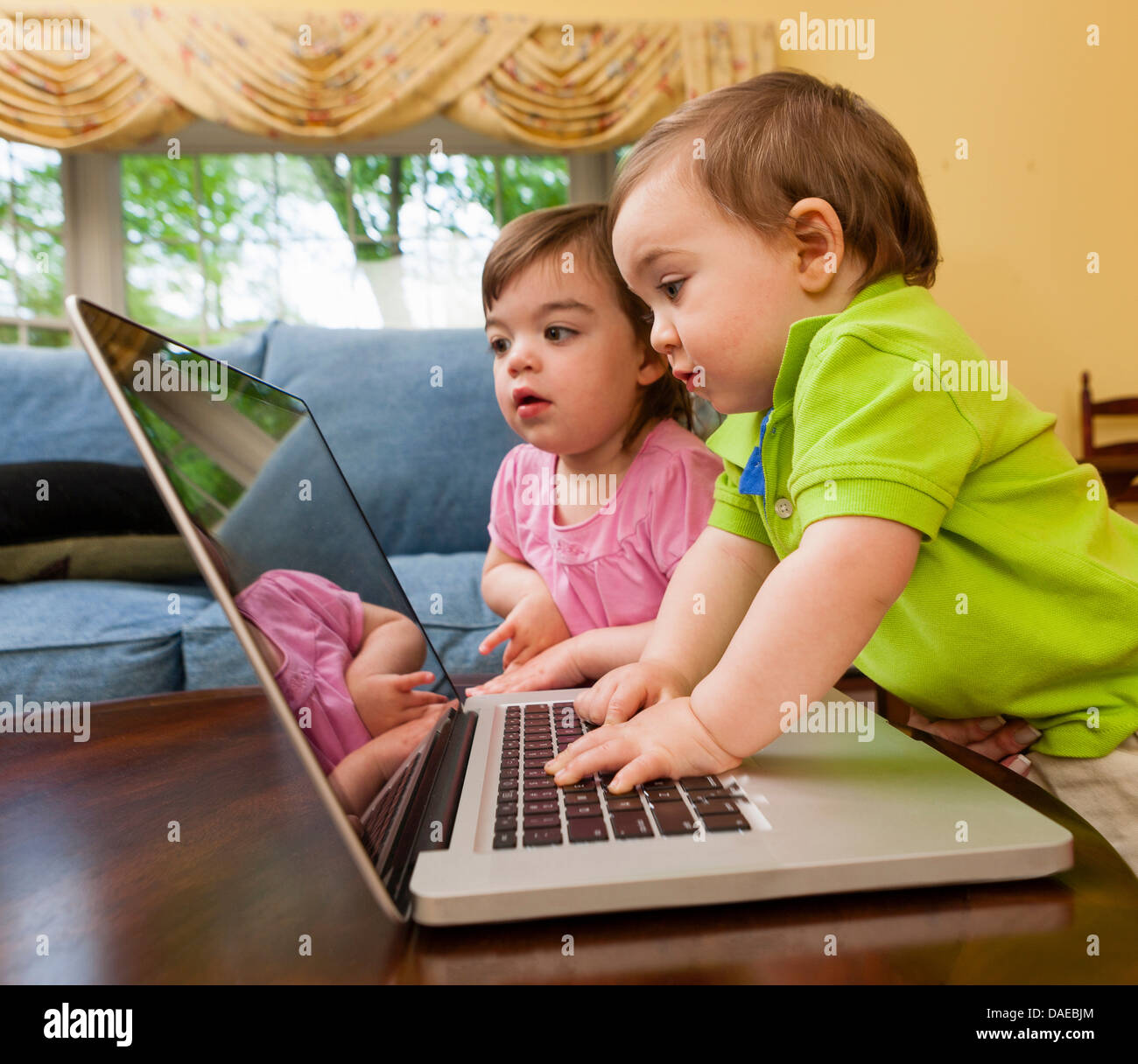 Two young toddlers playing with laptop - Stock Image