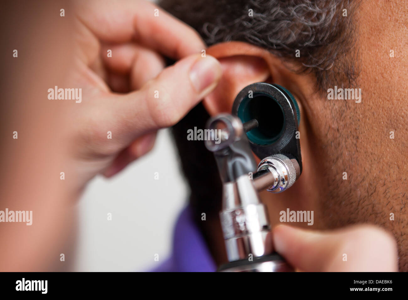Mid adult doctor using otoscope on patient - Stock Image