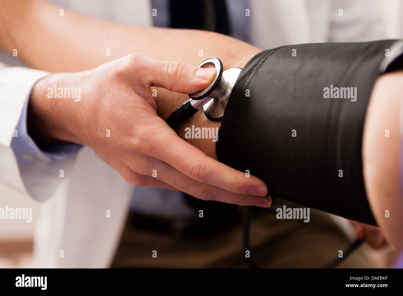 Mid adult doctor using stethoscope and blood pressure cuff on patient, close up - Stock Image