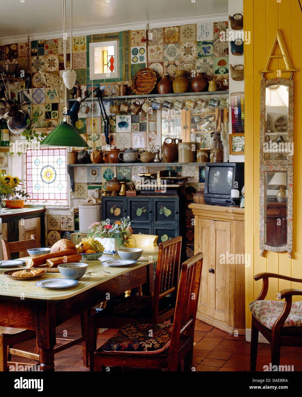 Old Pine Table And Chairs In Cluttered Cottage Kitchen With Narrow Mirror On The Wall Stock Photo Alamy
