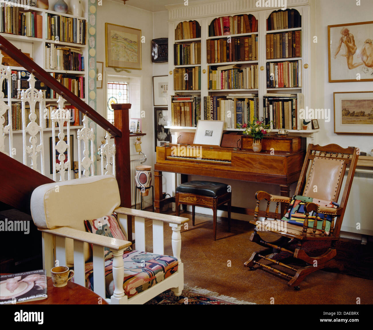 Antique spinet below fitted bookcase in cottage living room with Edwardian  rocking chair and painted wooden armchair - Antique Spinet Below Fitted Bookcase In Cottage Living Room With