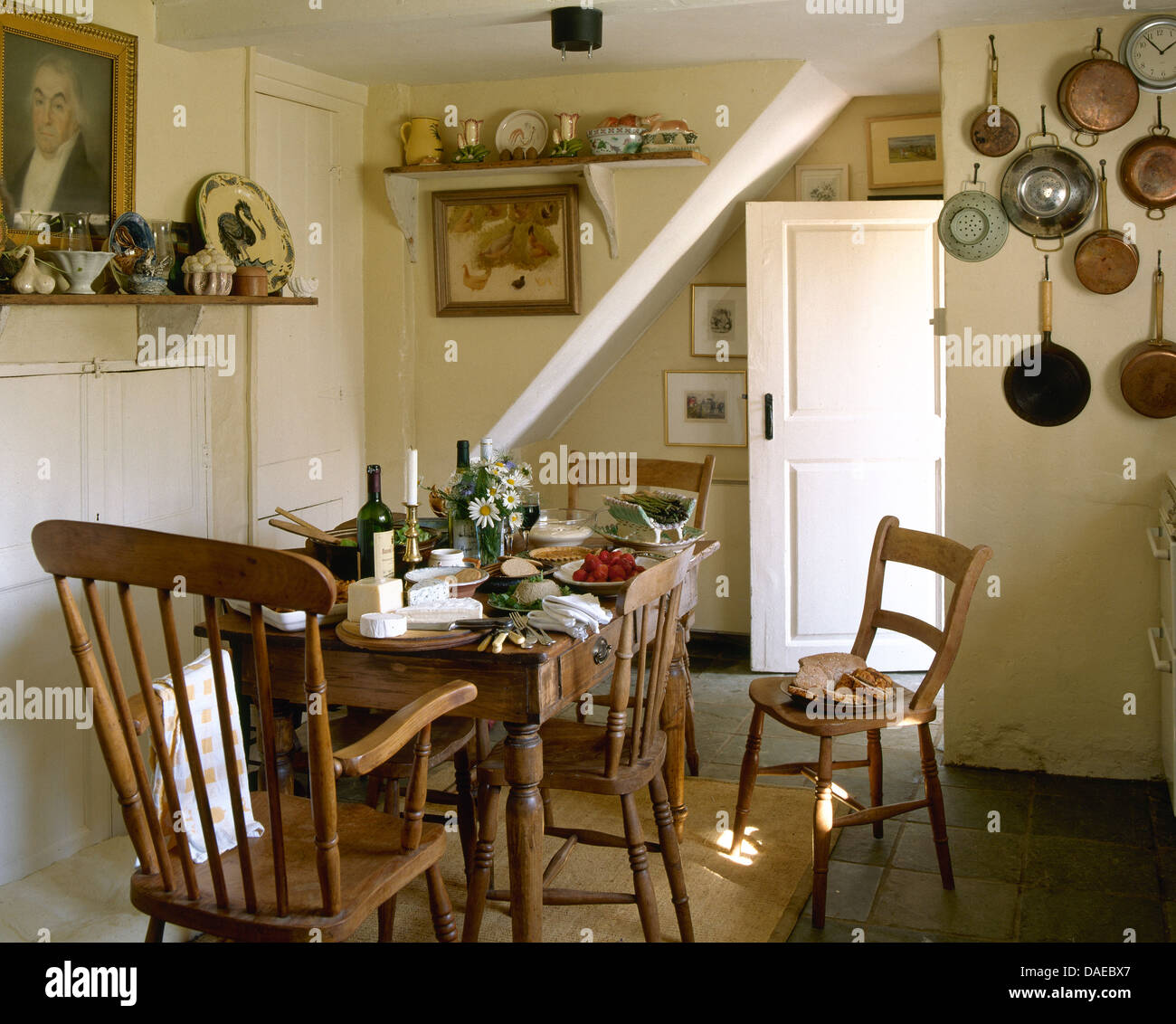 cottage kitchen furniture. Simple Wooden Chairs And Old Pine Table Set For Lunch In Cottage Kitchen With Pans Hanging On The Wall Furniture A