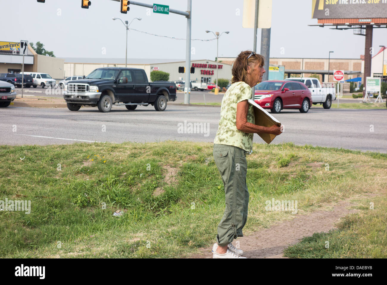 An old, homeless woman holding a sign begs at an intersection in Oklahoma City, Oklahoma, USA in a high traffic - Stock Image