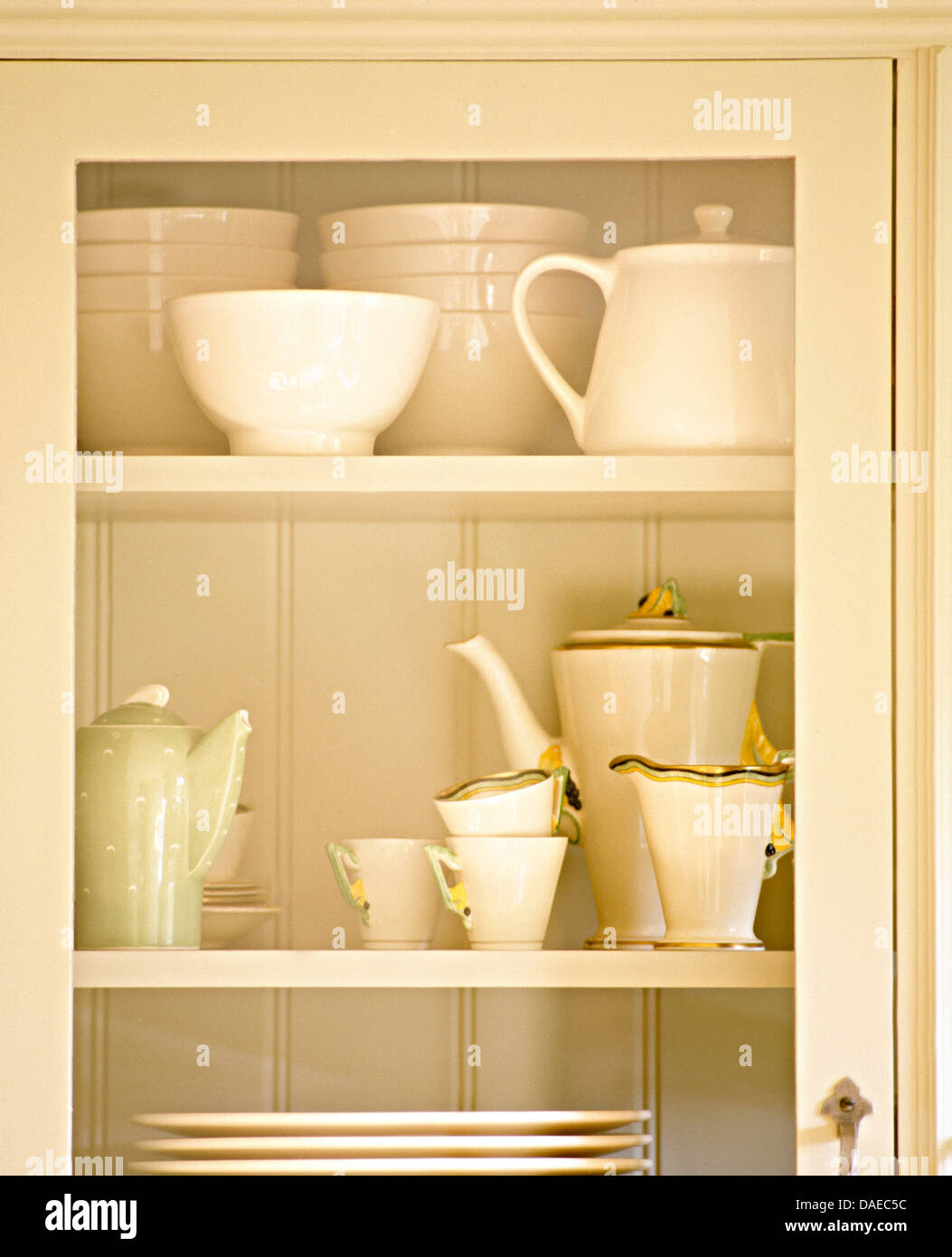 Glass door on recessed kitchen cupboard with cream bowls and an Art ...