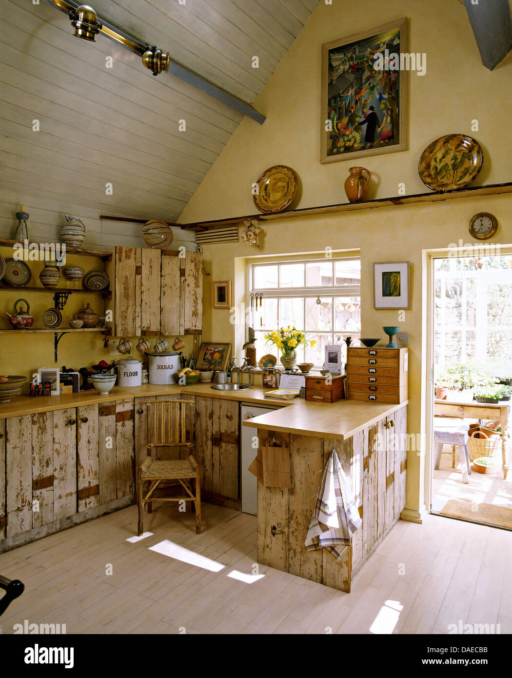 Genial Rustic Country Kitchen With Salvaged Wood Cupboards, A Pitched Roof, And  Conservatory Beyond