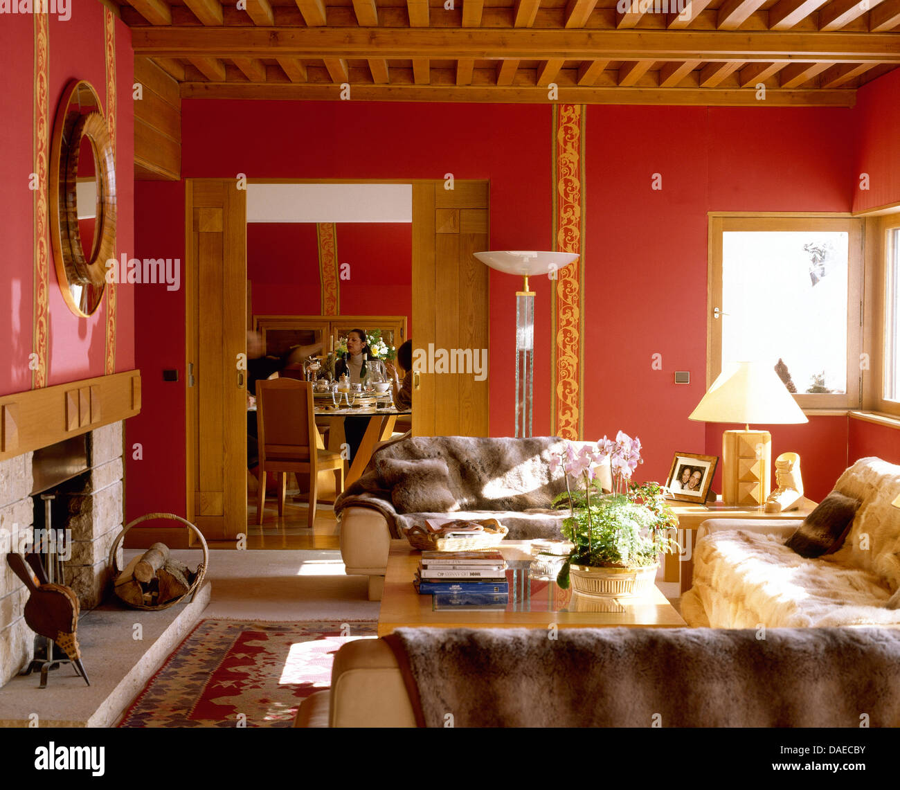 Faux Fur Rugs On Sofas In Red Alpine Living Room With Wooden Beamed