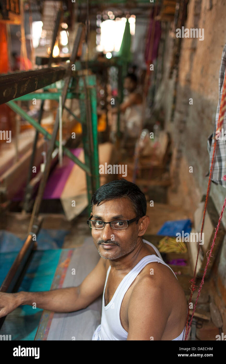 A man operates the loom making Jamdani sari in Mirpur Benarashi Palli, Dhaka, Bangladesh, a poor Bengali neighborhood. - Stock Image