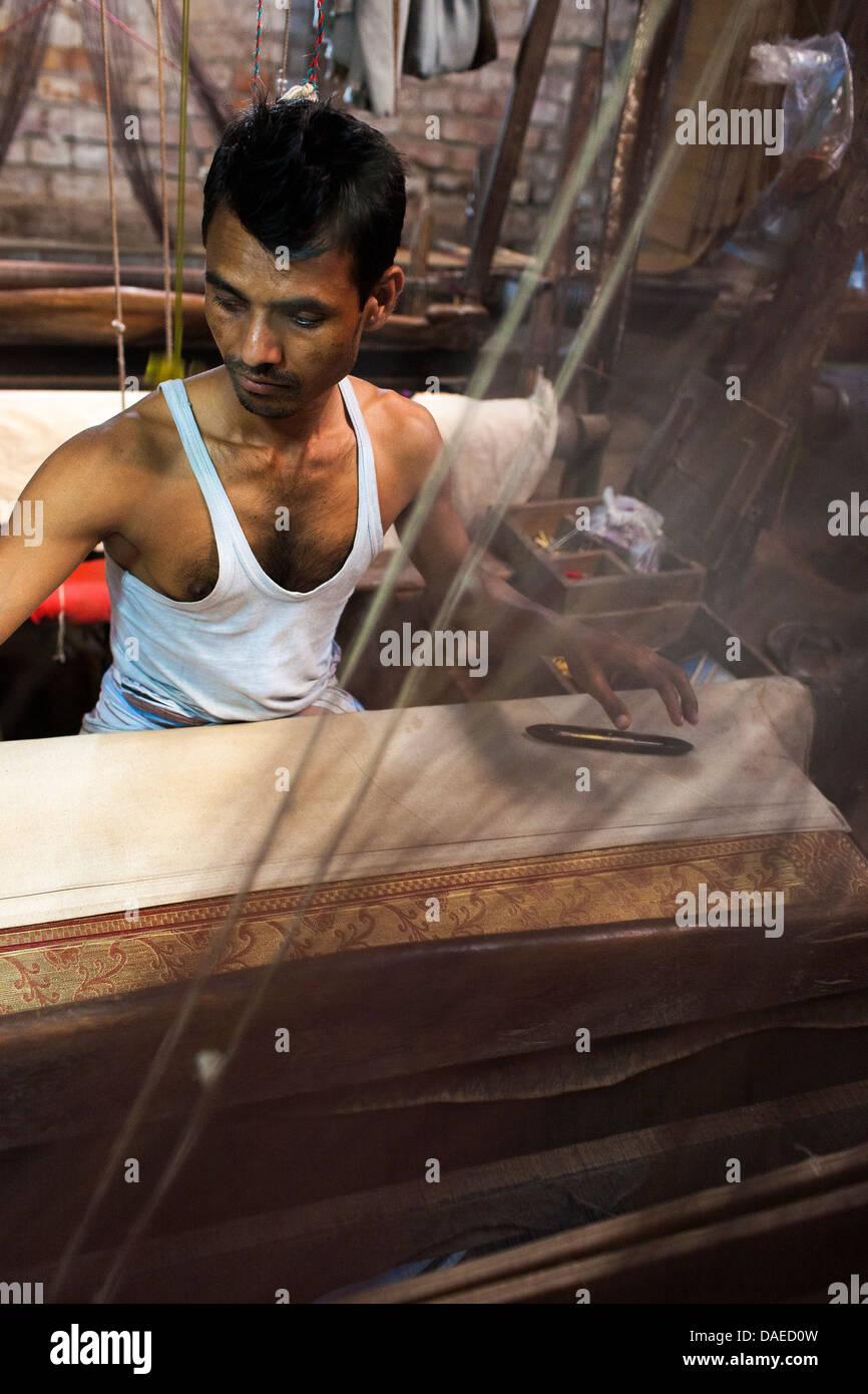 A man operates the loom making Jamdani sari in Mirpur Benarashi Palli, Dhaka, Bangladesh, a poor Bengali neighborhood. - Stock Image