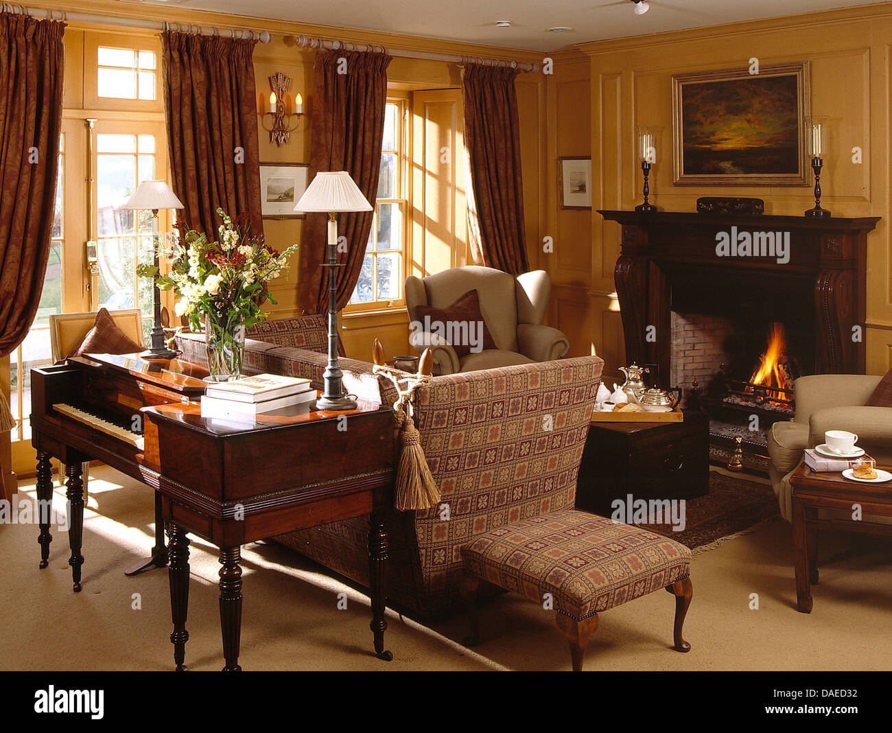 Antique Spinet Piano Behind Knole Sofa In Comfortable Country Sitting Room  With Lighted Fire In Fireplace