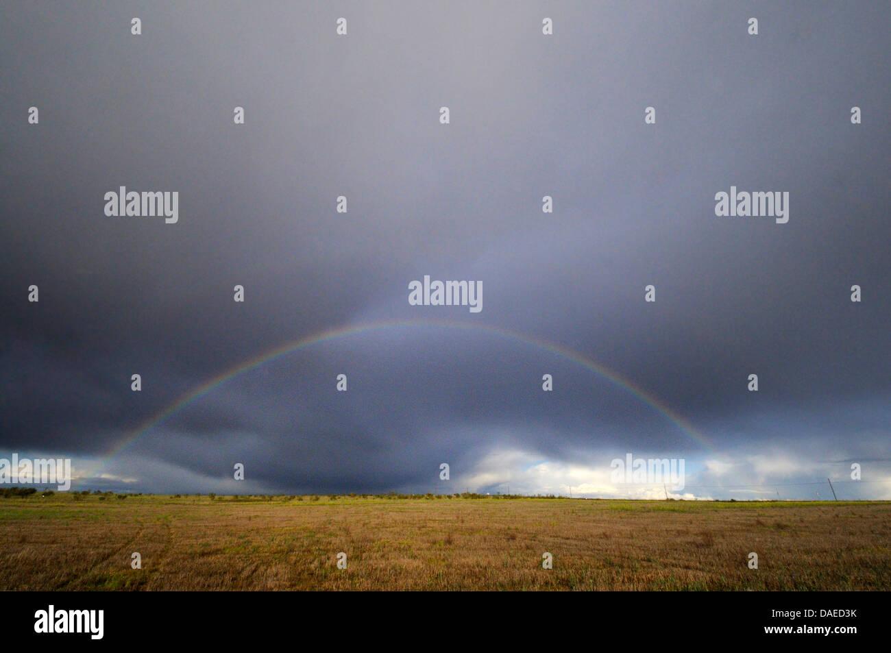 rainbow and dark clouds over steppe, Spain, Extremadura, Talavan - Stock Image