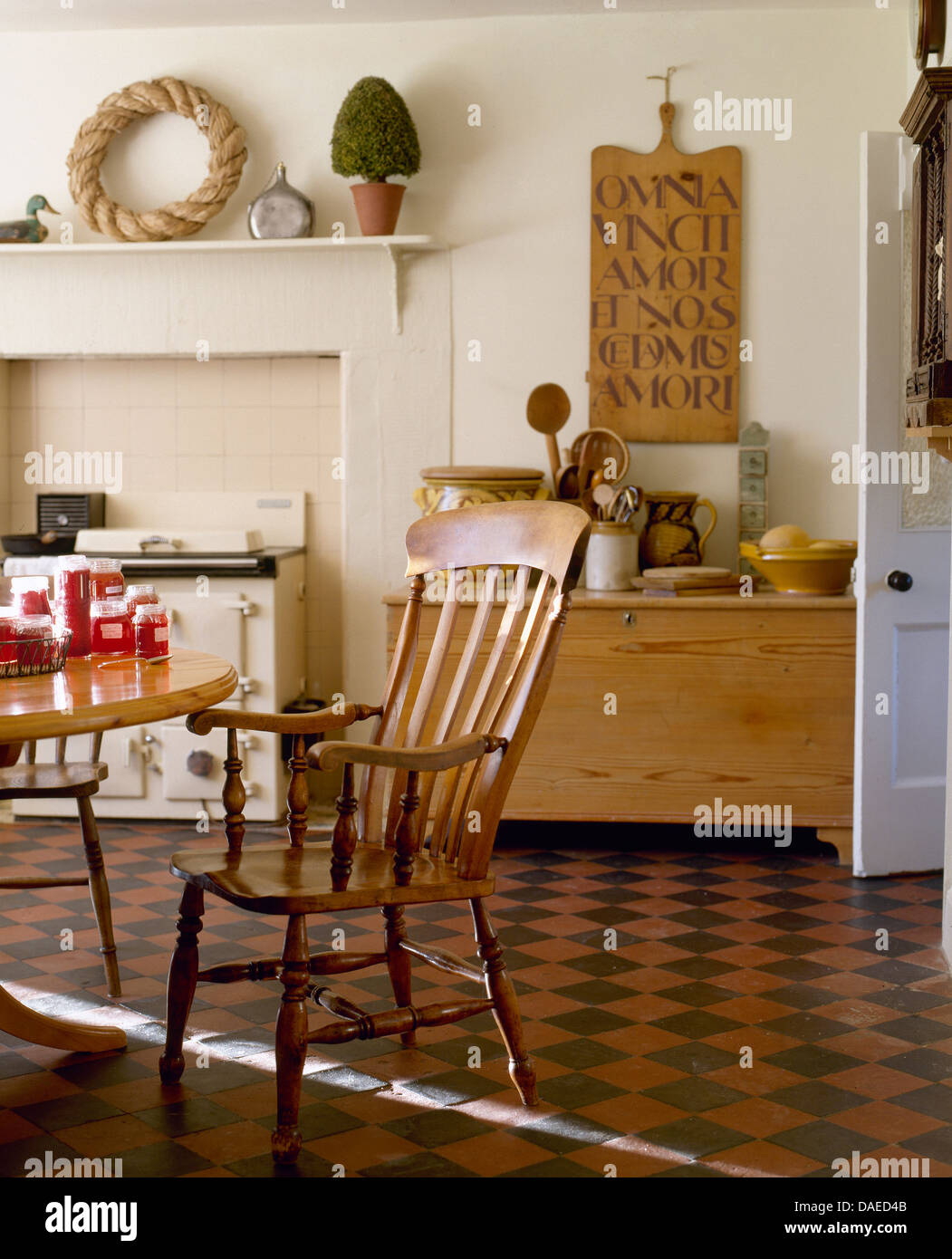 Antique Windsor chair in country kitchen with original black+red tiled  floor and wooden sign board above old pine chest - Antique Windsor Chair In Country Kitchen With Original Black+red