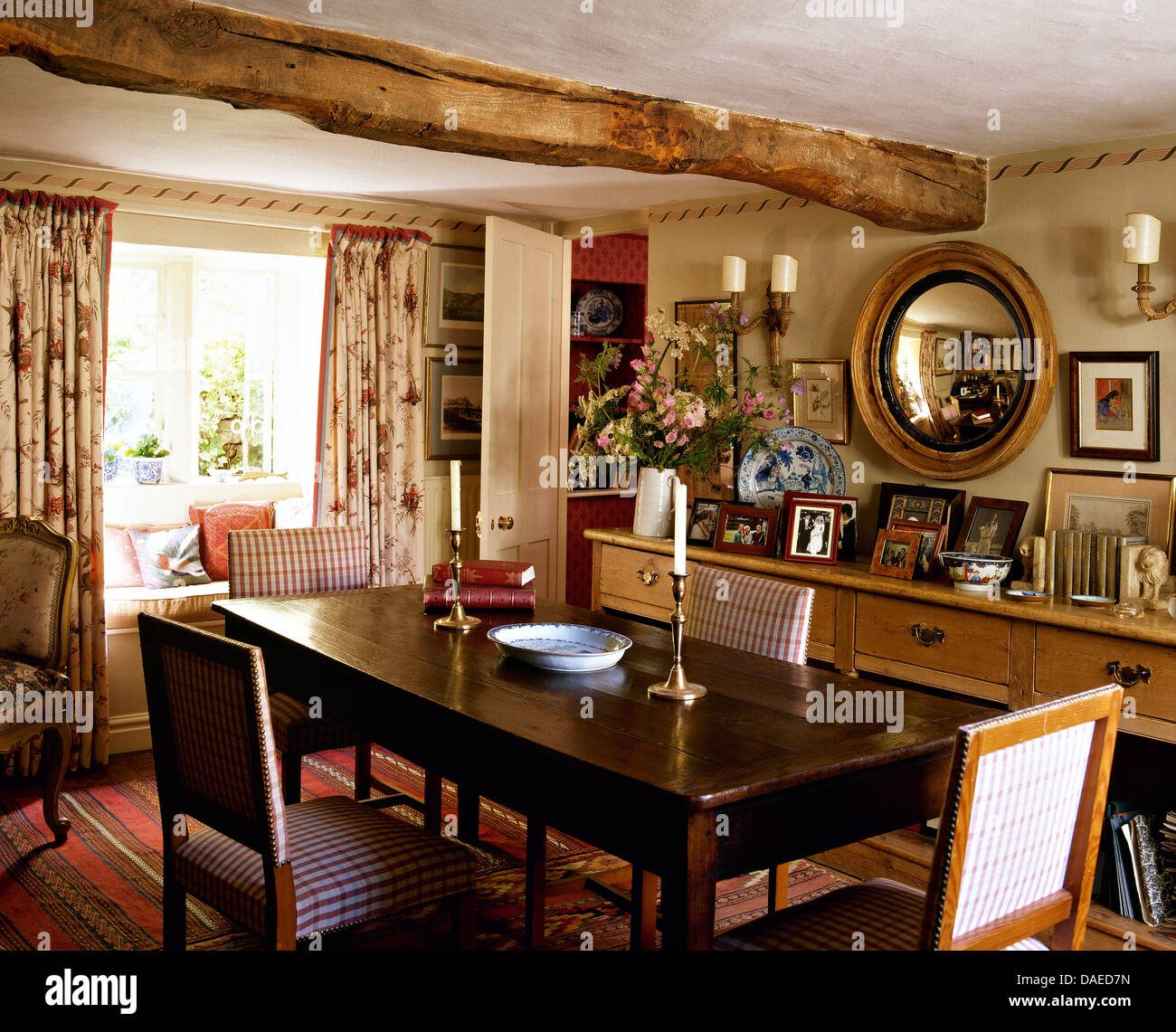 Upholstered chairs at antique oak table in cottage dining room with