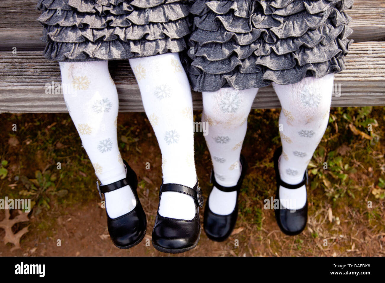 Two Girls in Matching Outfits Dangling Legs on Bench - Stock Image