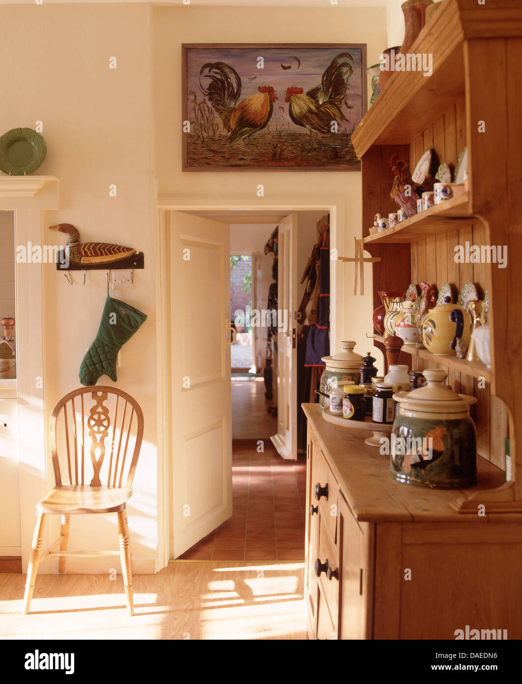 Display Of Pottery On Small Pine Dresser In Country Dining Room With Windsor Chair Beside Open Way
