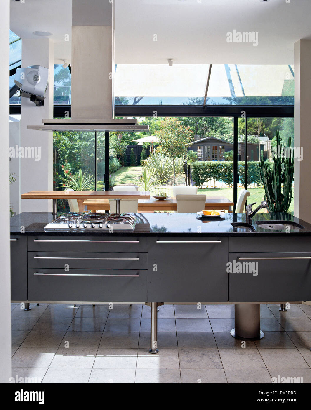 Etonnant Extractor Fan Above Gas Hob In Black Central Unit In Modern Kitchen With  View Of The Garden Through Large Window