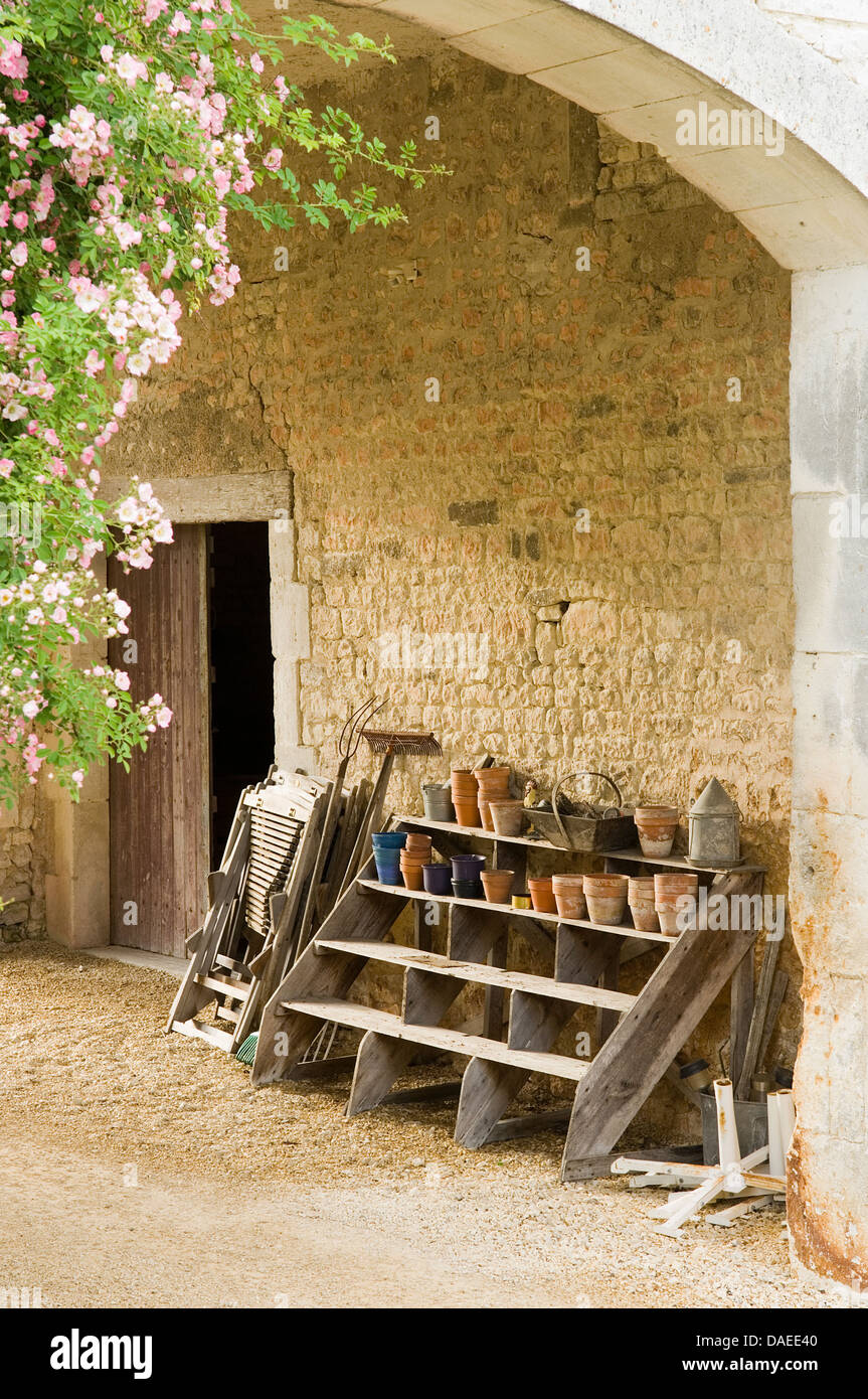 Terracotta flower pots on rustic wooden steps against wall in arched ...