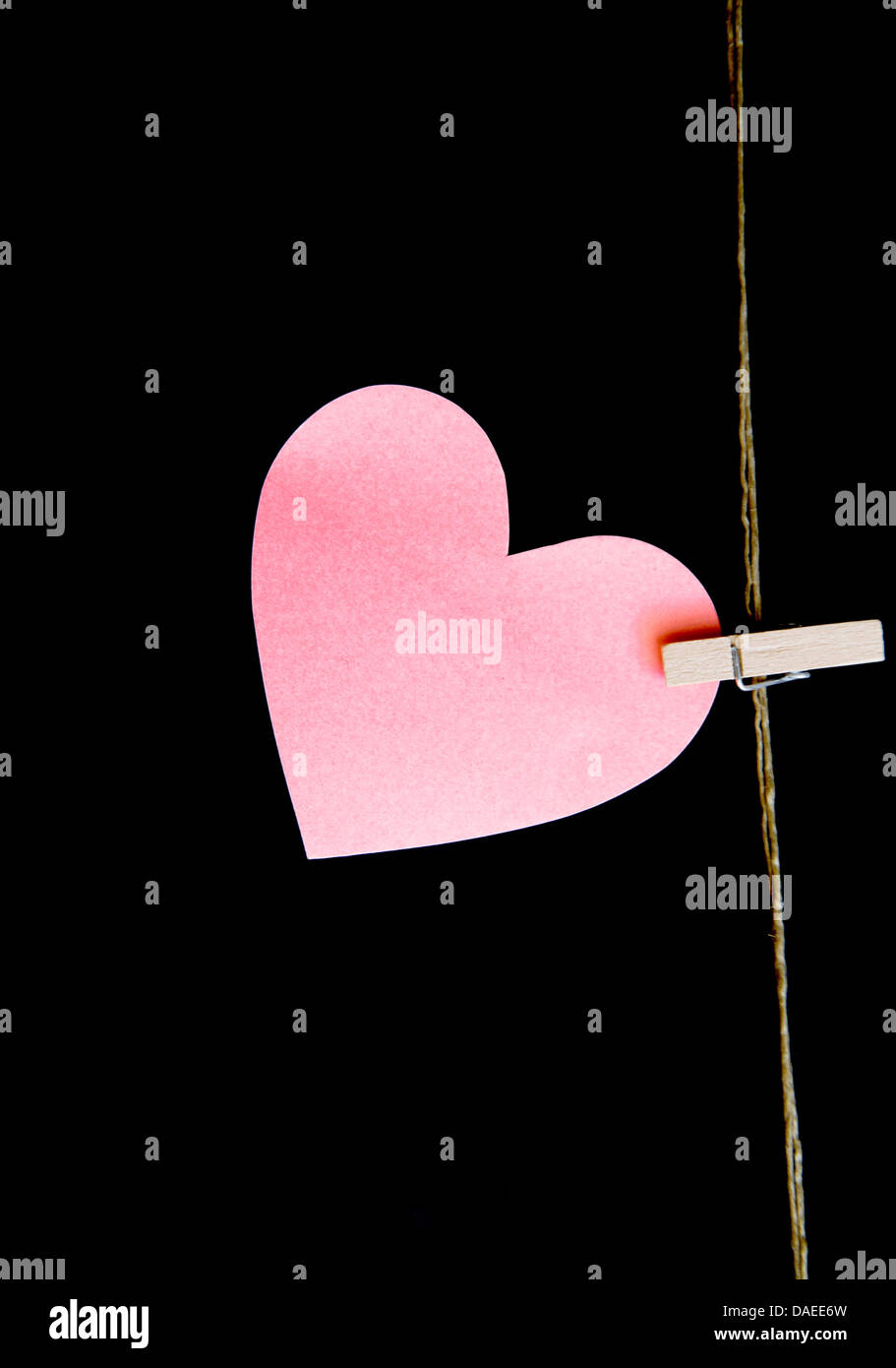 heart with clothespin on black background - Stock Image