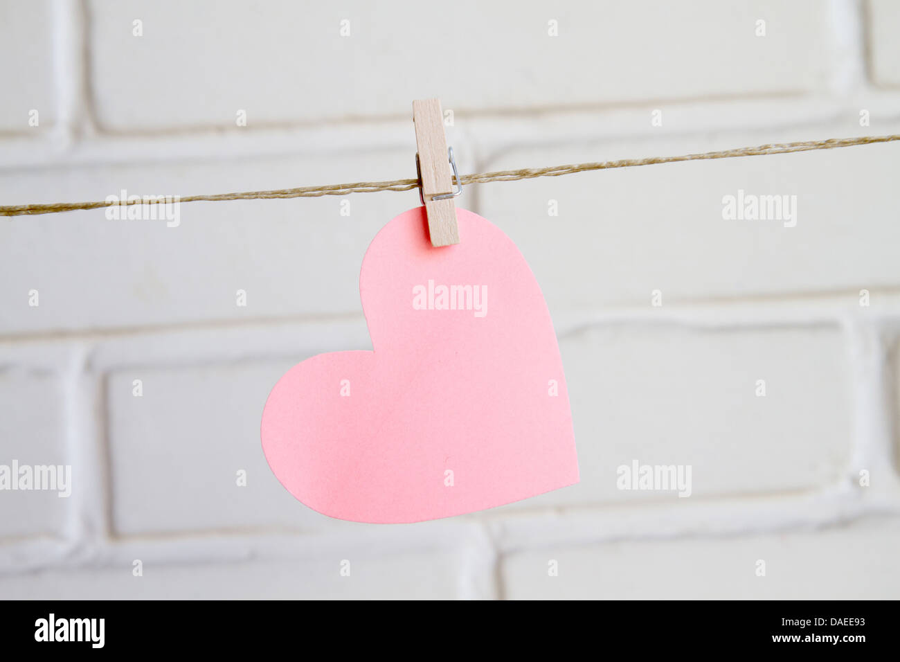 heart with clothespin on white background wall - Stock Image