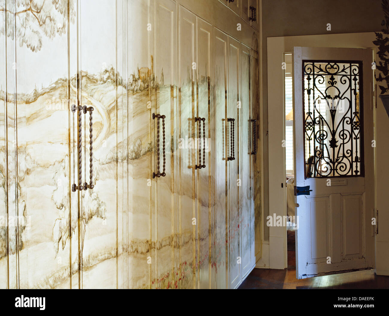 Lovely Landscape Mural Painted On Fitted Cupboards In Hall With Ornate Wrought  Iron Grille In Door