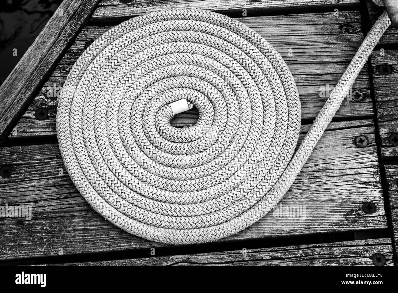 Coil of nylon rope on a pier - Stock Image