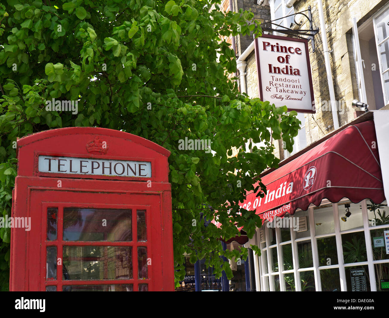 British traditional red telephone box outside a typical Indian Curry House England UK - Stock Image