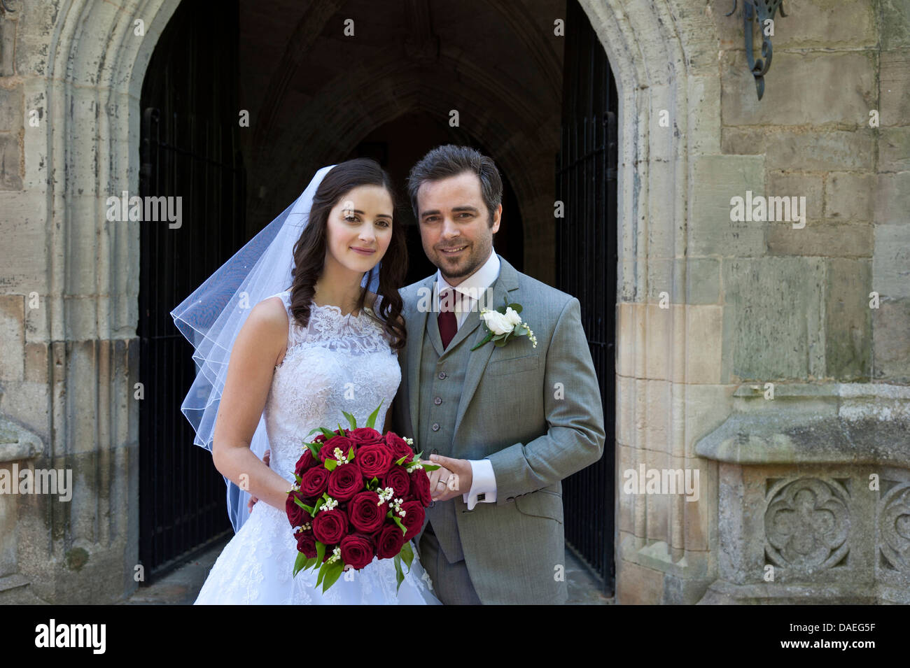 Attractive happy young traditional Bride and Groom just married standing outside the church door - Stock Image