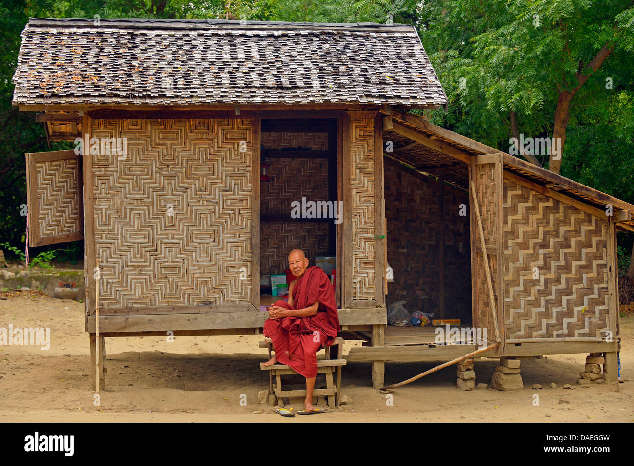 old monk on the stairs of his humble wooden house, Burma, Mandalay - Stock Image