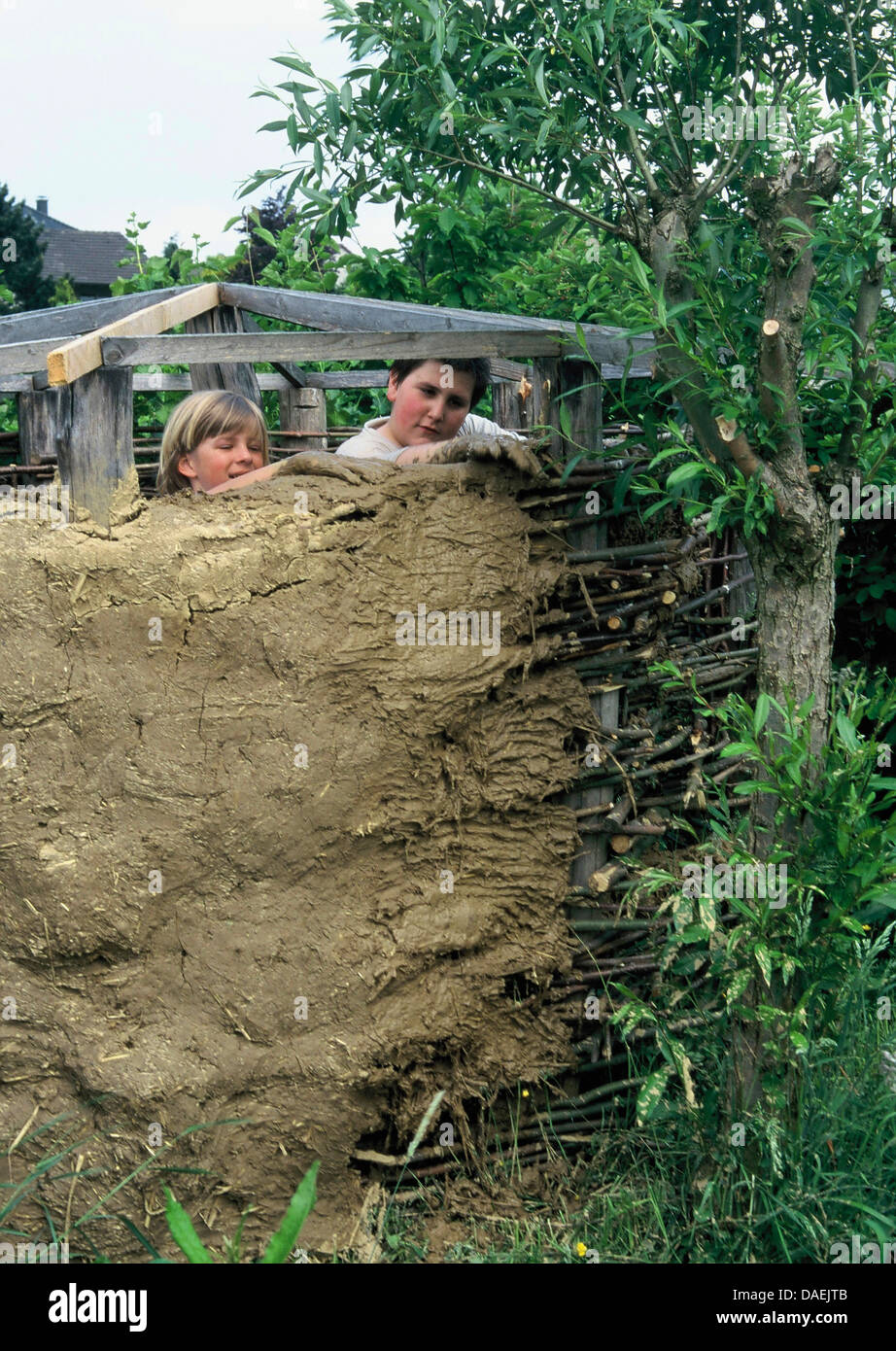 Two Boys Building A Clay Hut In The Garden, Germany