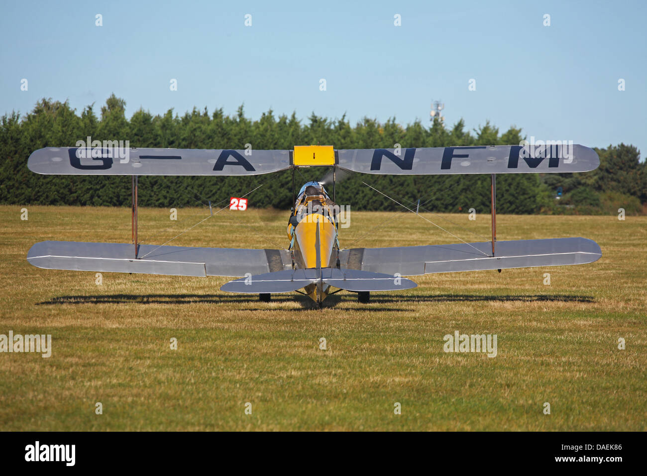 A biplane readying for taxiing to the runway on a fine day. - Stock Image
