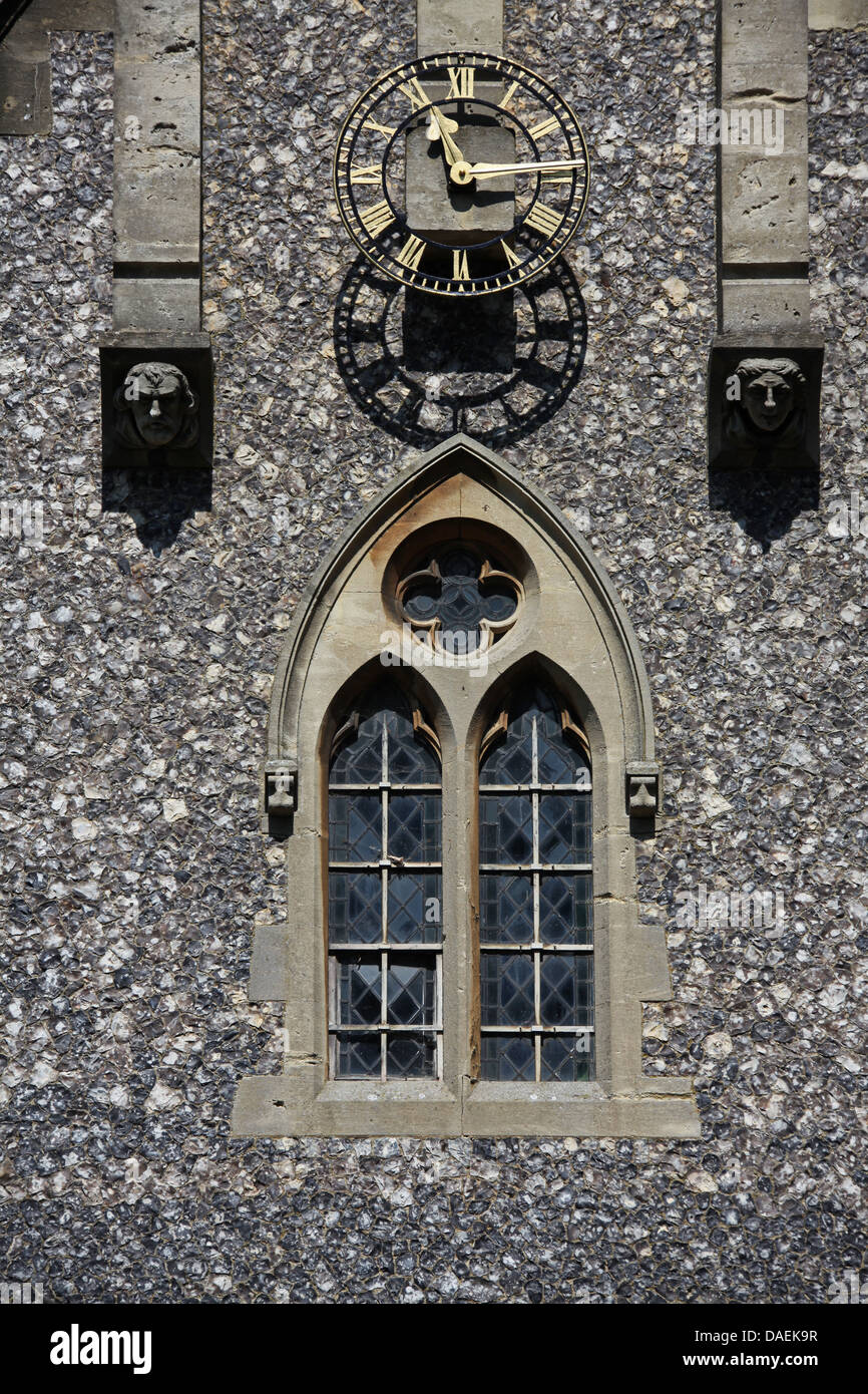 A large clock on a church building with a lead glass window below and two stone carved faces straddling the clock. - Stock Image