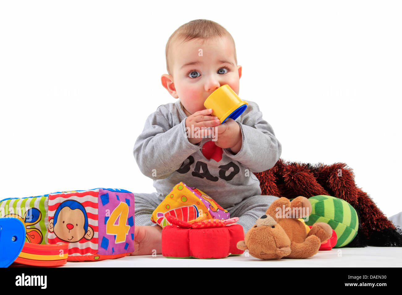 sitting baby playing lively with playthings - Stock Image