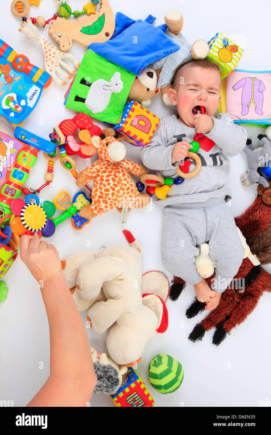 weeping baby lying between toys Stock Photo