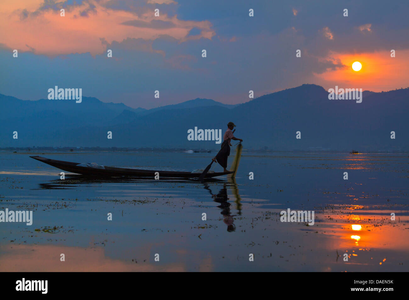 FISHING at dawn is still done in the traditonal way with small wooden boats, fishing nets and leg rowing - INLE - Stock Image