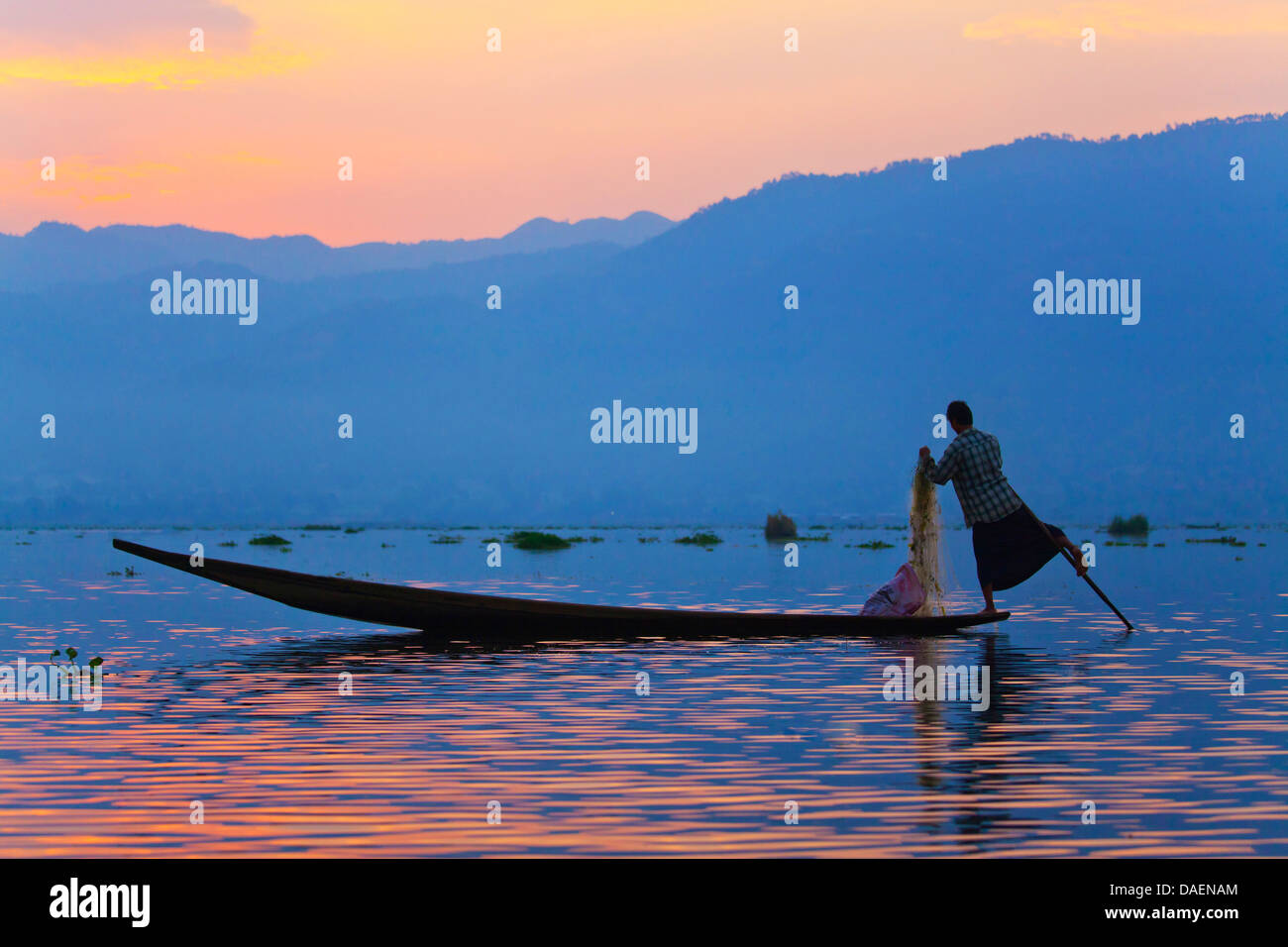 FISHING at dawn is still done in the traditonal way with small wooden boats, fishing nets and leg rowing, Inle Lake, - Stock Image