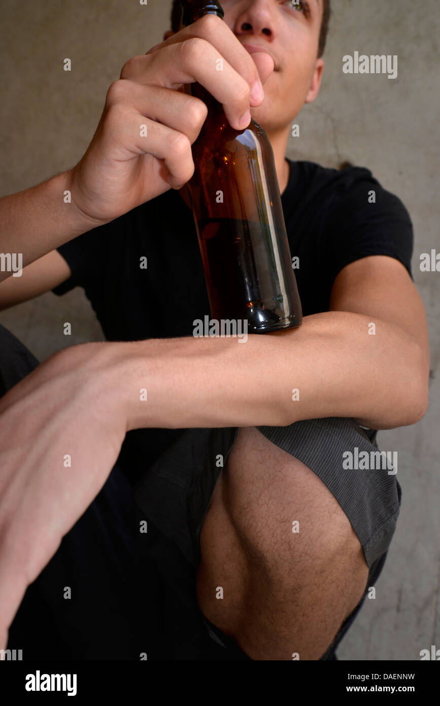 An 18-year-old male with a beer bottle. - Stock Image