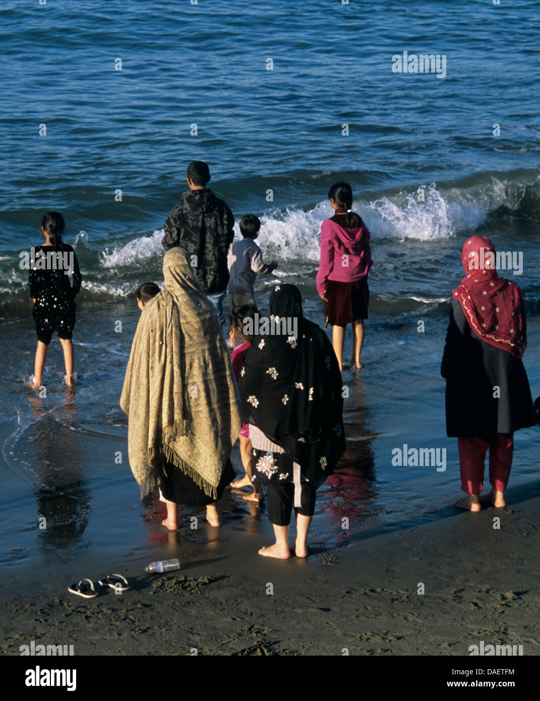 muslim family stand barefoot in pacific ocean on california coast at ocean beach - Stock Image