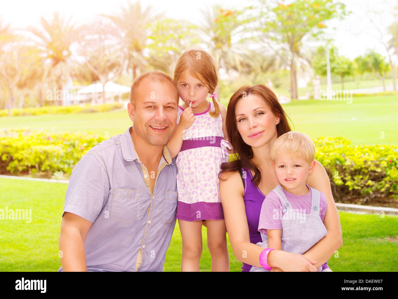 Portrait of cute family in spending time together in the park, happy young parents with two adorable child outdoors - Stock Image