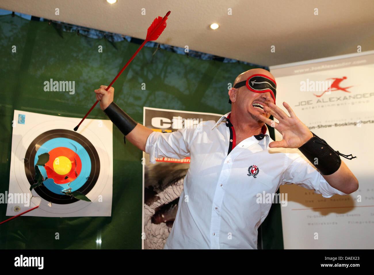 Stuntman Joe Alexander catches an arrow shot from a bow blindfolded in Hamburg,Germany, 16 November 2011. - Stock Image