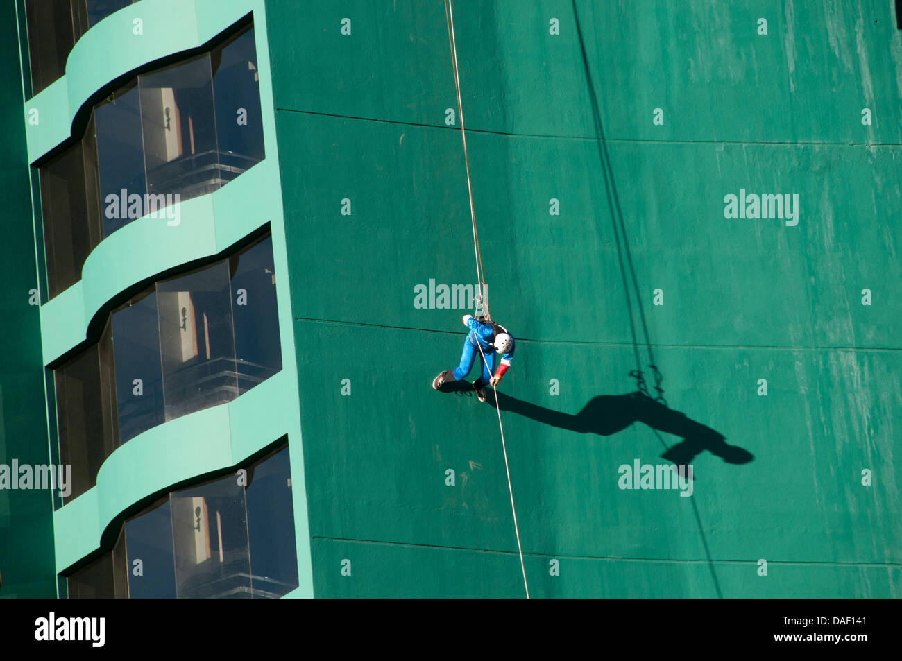 La Paz, Bolivia. Urban Rush tourist attraction. A thrill seeker dressed as spiderman jumps off the 17 storey Hotel - Stock Image