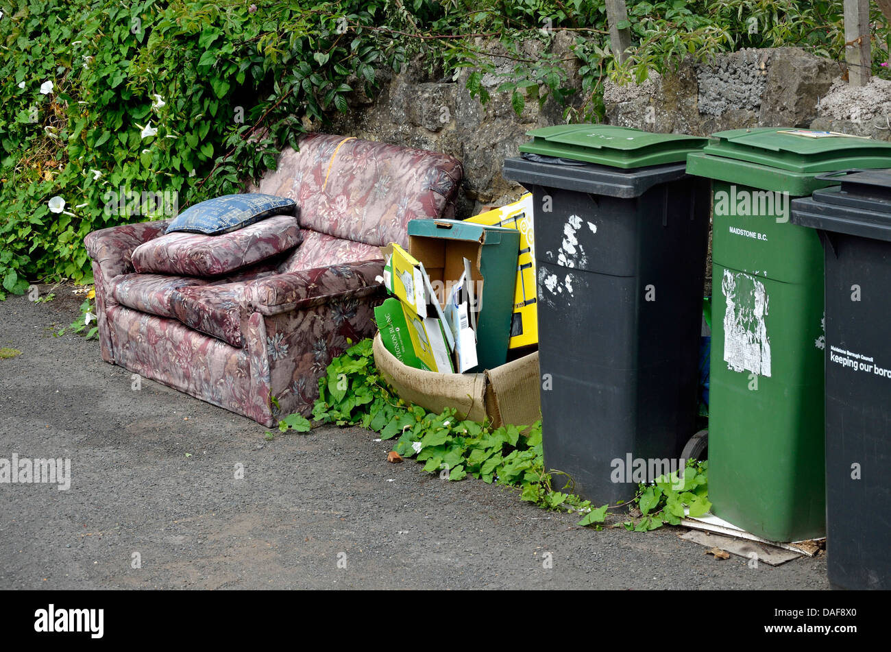 Maidstone, Kent, England. Household rubbish bins and discarded furniture - Stock Image