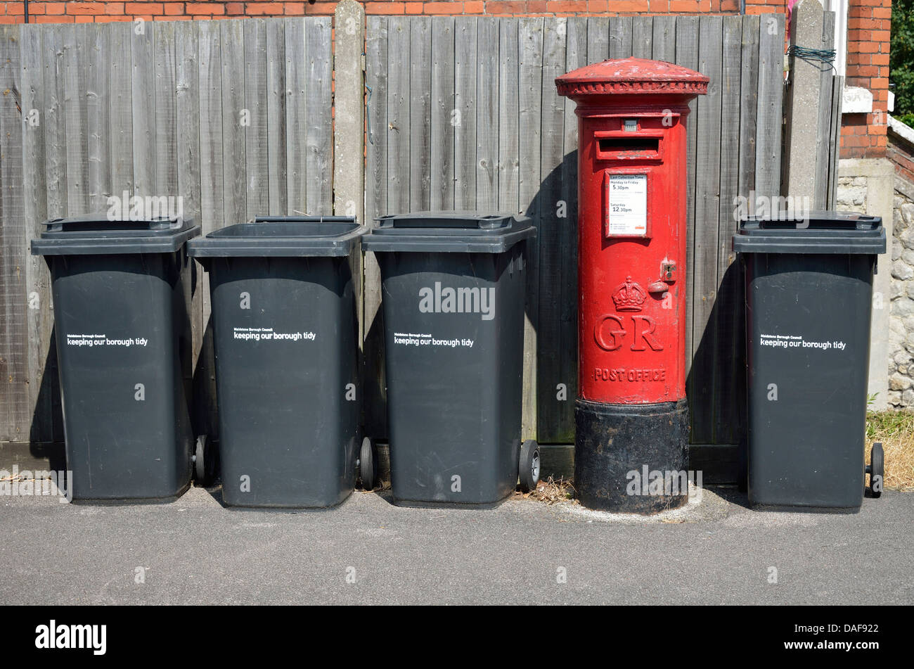 Maidstone, Kent, England. Row of household rubbish bins and red letterbox - Stock Image