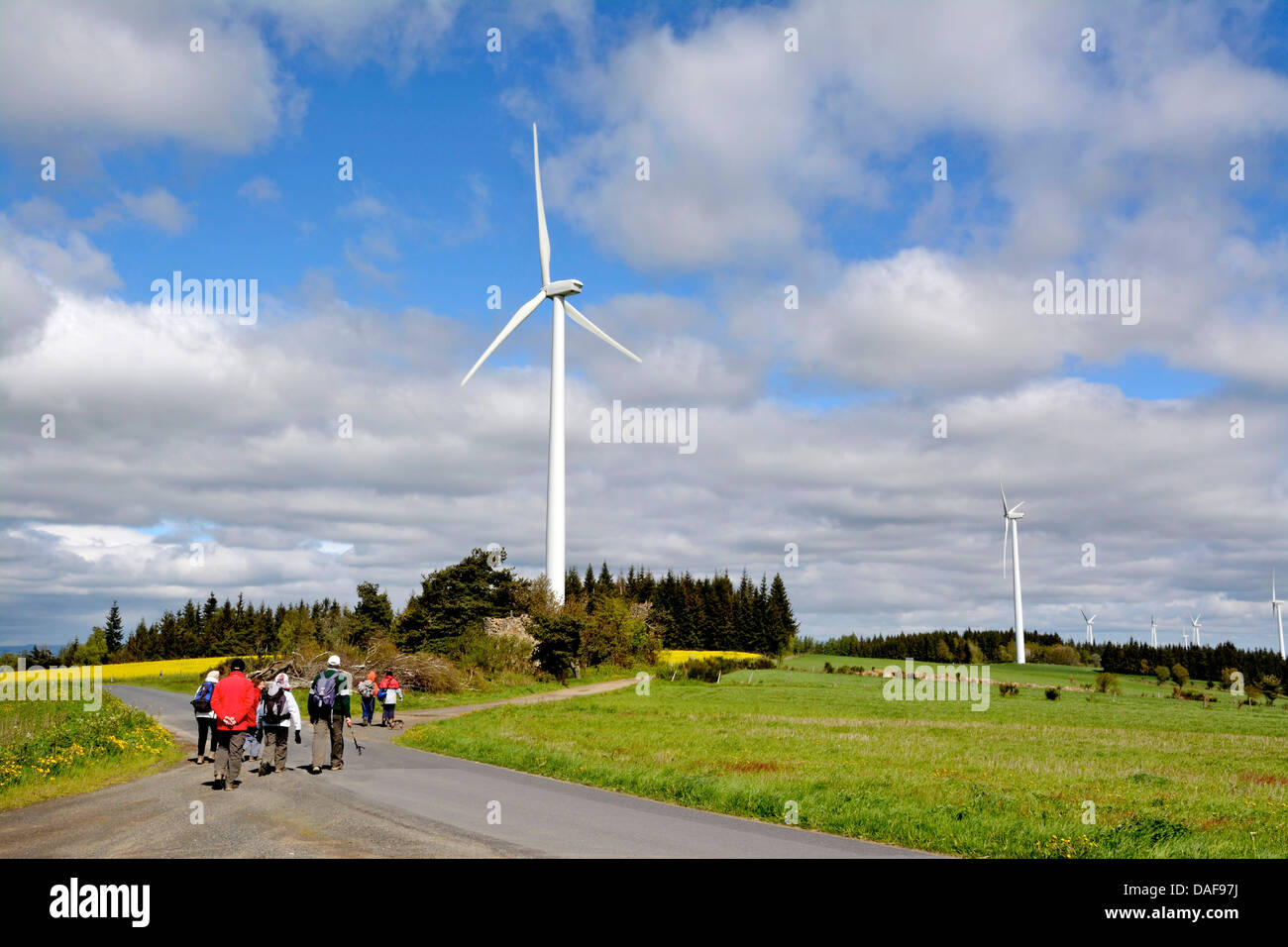 Hikers near a rural wind farm - Stock Image