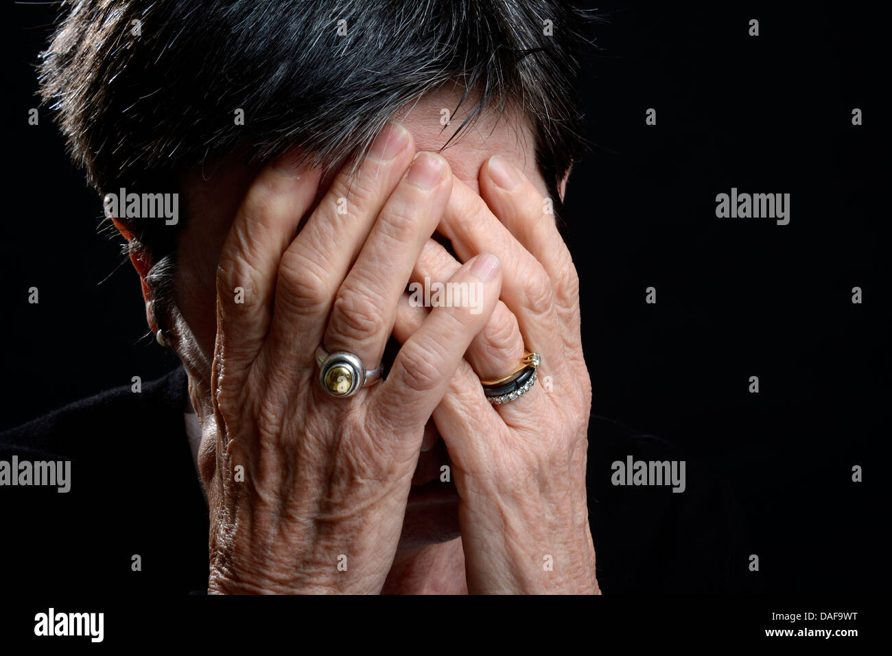 Sad old woman covering her face with her hands / crying, mental health concept - Stock Image