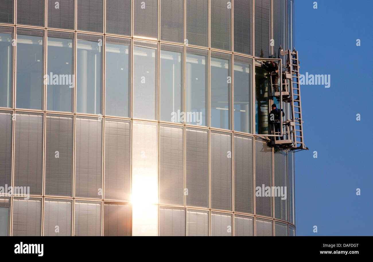 Construction workers repair a window at a high-riser in Duesseldorf, Germany, 22 February 2011. Photo: Rolf - Stock Image