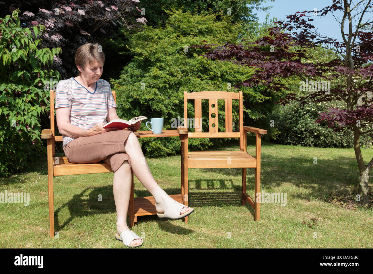 Senior retired woman retiree sitting alone reading a book outdoors beside an empty seat in a back garden on a sunny - Stock Image