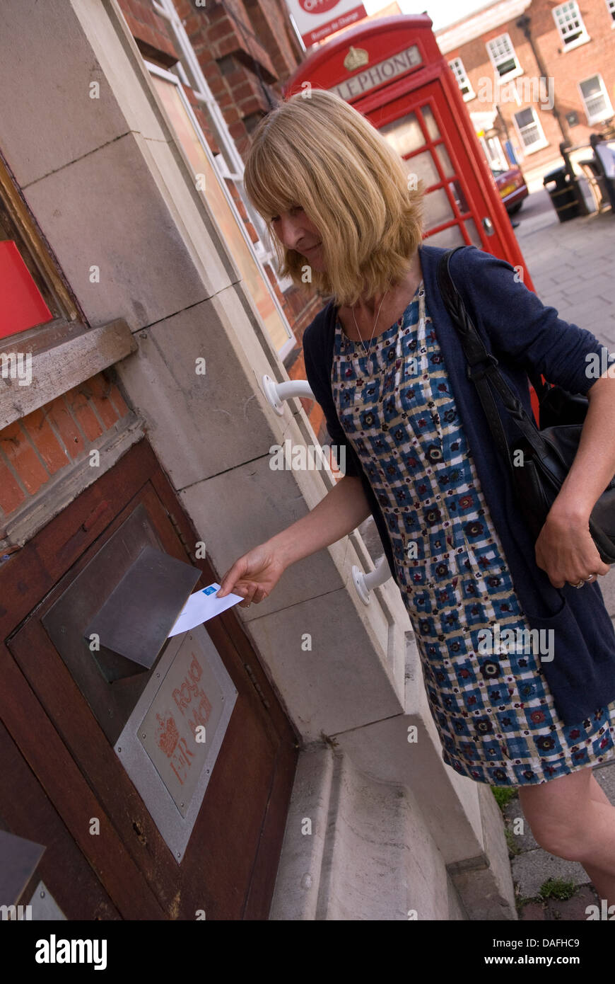 Woman posting a second class letter in main post office, Petersfield, Hampshire, UK. - Stock Image