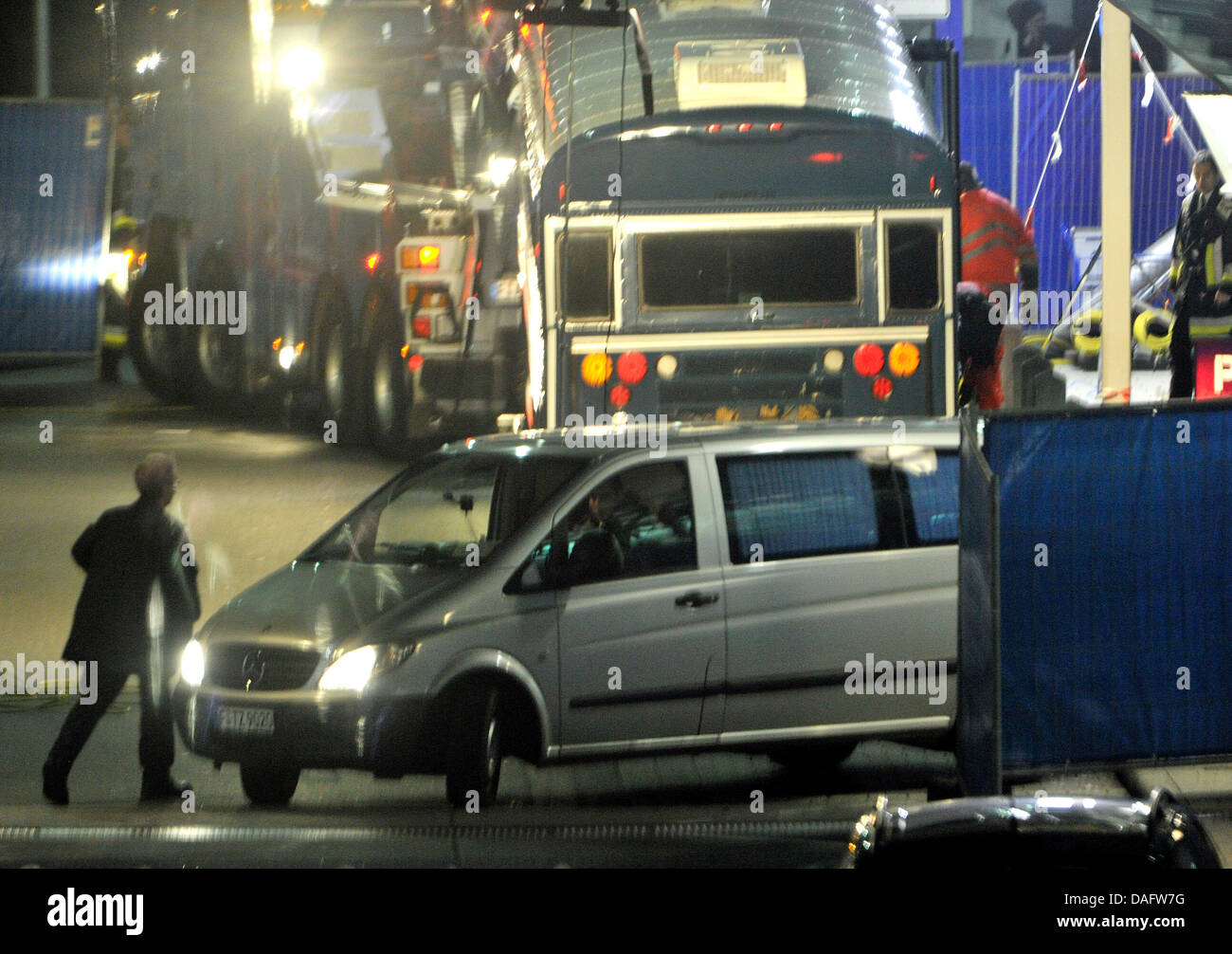 A coroner's car transports the bodies of the two vicitms away from the crime scene with the bus in the background - Stock Image