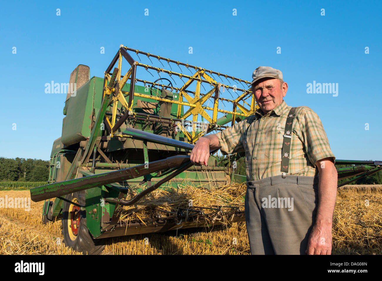 farmer in front of his old combine harvester in grain field, Germany - Stock Image