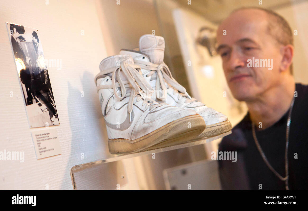 An employee stands next to the sport shoes of German politician Joschka Fischer, in which he was signed in as German - Stock Image